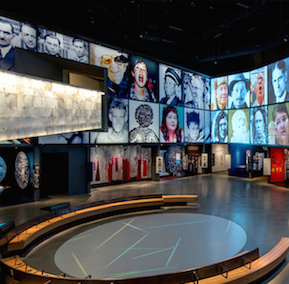 A large gallery with pictures of people shown on an overhead screen
