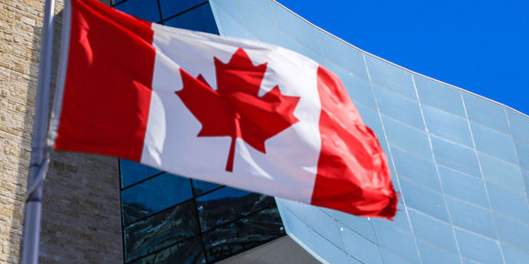 Canadian flag waving in front of the Canadian Museum for Human Rights; bright blue sky in the corner.