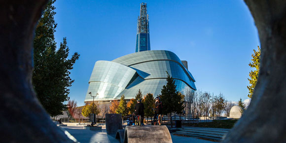 Canadian Museum for Human Rights building flanked by autumn trees.
