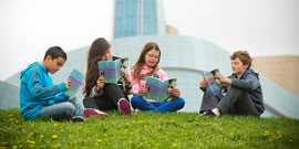 Four children each reading a book on a grassy hill in front of the Canadian Museum for Human Rights.