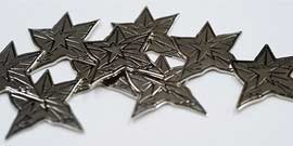 Close-up of silver metallic embossed stars, slightly imperfect in shape.