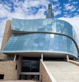 Canadian Museum for Human Rights building façade; a stone base is encircled with hundreds of windows that together resemble two overlapping ribbons.